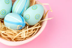 Happy easter composition. Nest with blue pained easter eggs. Texture pink background. Flat lay, top view and copyspace Royalty Free Stock Photos