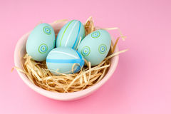 Happy easter composition. Nest with blue pained easter eggs. Texture pink background. Flat lay, top view and copyspace Stock Image