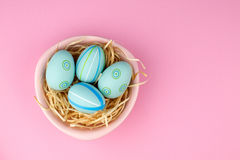 Happy easter composition. Nest with blue pained easter eggs. Texture pink background. Flat lay, top view and copyspace Stock Photo