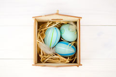 Happy easter composition. Nest with blue pained easter eggs. Texture rustic white wooden background. Flat lay, top view and copysp Stock Photography