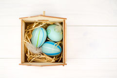 Happy easter composition. Nest with blue pained easter eggs. Texture rustic white wooden background. Flat lay, top view and copysp Royalty Free Stock Photo
