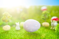 Happy Easter concept. Baby Easter bunny on spring green grass. Fairy tale sunset on the plastic green field with plastic grass, mu Stock Photos