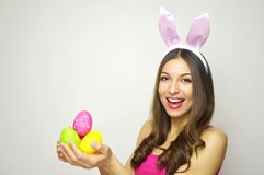 Happy Easter concept. Beautiful young woman with bunny ears holdings colorful Easter eggs on white background. Copy space. Happy Easter concept. Beautiful young Stock Images