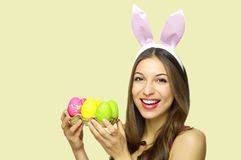 Happy Easter concept. Happy cheerful woman with bunny ears holdings egg carton of colorful Easter eggs looking at camera over yell. Ow background. Copy space Stock Photography