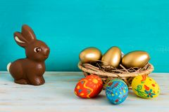 Happy Easter concept with color ang gold eggs in basket next to chocolate Easter bunny on blue wooden background royalty free stock photos