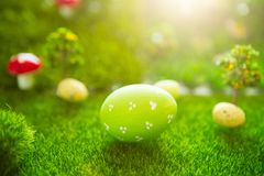 Happy Easter concept. Colorful easter eggs and one big green easter egg on spring green grass. Fairy tale sunset on the plastic gr Stock Photography