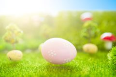 Happy Easter concept. Colorful easter eggs and one big pink easter egg on spring green grass. Fairy tale sunset on the plastic gre Stock Images