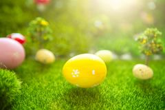 Happy Easter concept. Colorful easter eggs and one big yellow easter egg on spring green grass. Fairy tale sunset on the plastic g Royalty Free Stock Images