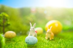 Happy Easter concept. Easter rabbits toy on spring green grass. Fairy tale sunset on the plastic green field with plastic grass, m Stock Photos