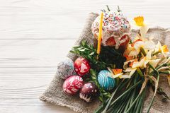 happy Easter concept. stylish painted eggs and easter cake on white rustic wooden background with spring flowers and candle. seas royalty free stock image