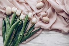 Happy easter concept. stylish white tulips and simple easter egg. S on rustic wooden background and fabric flat lay. greeting card with space for text, top view Stock Images