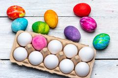Happy Easter - container with white and colored eggs stock photography
