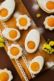 Cookies in the shape of white eggs with apricot yolk as homemade decoration. Happy Easter. Cookies in the shape of white eggs with apricot yolk as homemade stock photos