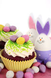 Happy Easter cupcakes. With bunny easter eggs on pink wood table Royalty Free Stock Photography