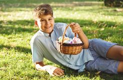 Happy Easter! Cute smiling boy teenager in blue shirt holds basket with handmade colored eggs on grass in spring park. Decoration royalty free stock images