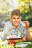 Happy Easter! Cute smiling boy teenager in blue shirt holds basket with handmade colored eggs on grass in spring park. Decoration stock photography
