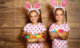 Happy easter! cute twins girls sisters dressed as rabbits with e. Ggs on wooden background royalty free stock photography