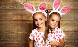 Happy easter! cute twins girls sisters dressed as rabbits on wo Royalty Free Stock Photo
