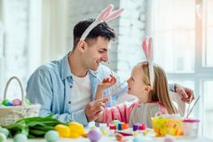 Happy easter!Dad and his little daughter together have fun while preparing for Easter holidays.On the table is a basket with. Easter eggs, flowers and paint stock images
