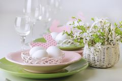 Happy easter. Decor and table setting of the Easter table is a vase with pink tulips and dishes of pink and green color. Selective focus stock image