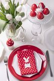 Happy easter. Decor and table setting of the Easter table is a vase with white tulips and dishes of red and white color. Easter. Colored eggs with white polka royalty free stock photo