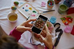 Happy easter decoration. Woman hands holding smartphone and making photo of colorful easter eggs on the table. Happy easter decoration. Woman hands holding royalty free stock images