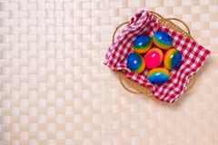 Happy easter decorations background. Top view of colorful easter eggs in a basket on checkered napkin on a light beige tablecloth royalty free stock images