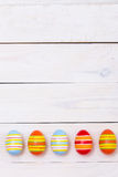 Happy Easter! Easter Colorful eggs on white wooden background. Top view with copy space Stock Images