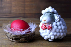 Happy Easter: Easter egg in the nest and little sheep Royalty Free Stock Photo