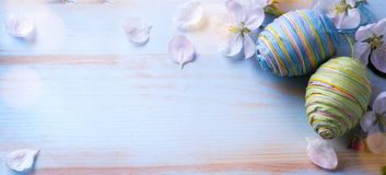 Happy Easter;  Easter eggs and sprig flowers on blue table backg Stock Images