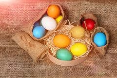 Easter colorful eggs in burlap sack and box Royalty Free Stock Image