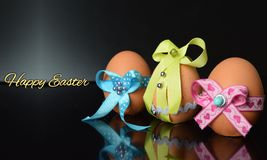 Happy Easter eggs with colored ribbons and pearls Royalty Free Stock Images