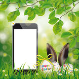 Happy Easter Eggs Smartphone Hare Ears Beech Twigs. Happy easter eggs with hare ears and smartphone in the green nature Stock Photo