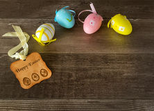 Happy Easter. Easter eggs with a tag on wooden background Royalty Free Stock Photos