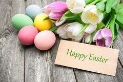 Happy Easter. Easter eggs and tulips with a tag on wooden background royalty free stock photo
