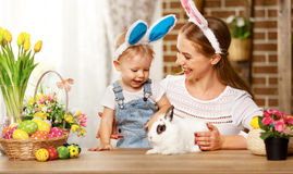 Happy easter! family mother and baby son playing with a rabbit a Stock Image