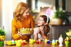 Happy easter! family mother and child daughter with ears hare getting ready for holiday royalty free stock photography