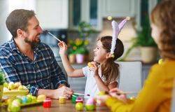 Happy easter! family mother, father and child daughter paint eggs for holiday. Happy easter! family mother, father and child daughter paint eggs for the holiday royalty free stock photography