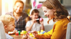 Happy easter! family mother, father and children paint eggs for holiday. Happy easter! family mother, father and children paint eggs for the holiday royalty free stock photography