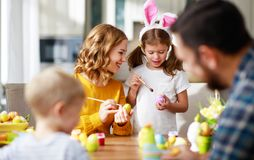Happy easter! family mother, father and children paint eggs for holiday stock photos
