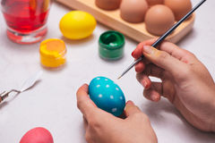 Happy Easter! Father painting Easter eggs on table. Royalty Free Stock Images