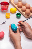 Happy Easter! Father painting Easter eggs on table. royalty free stock image