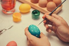 Happy Easter! Father painting Easter eggs on table. stock photos