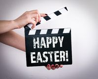 Happy Easter. Female hands holding movie clapper stock photography