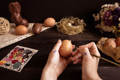 Happy easter. Female hands painting easter egg on the wooden table Royalty Free Stock Photos