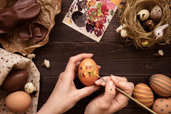 Happy easter. Female hands painting easter egg on the wooden table Royalty Free Stock Images