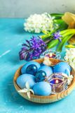 Happy Easter festive greeting card in blue style. Easter greeting card with colored blue eggs, quail eggs and candles in wooden plate in front of white and blue royalty free stock photography