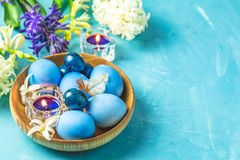 Happy Easter festive greeting card in blue style. Easter greeting card with colored blue eggs, quail eggs and candles in wooden plate in front of white and blue royalty free stock image