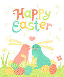 Happy Easter festive postcard with rabbits painted eggs on a meadow. Royalty Free Stock Images