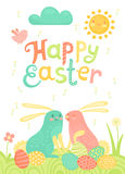 Happy Easter festive postcard with rabbits painted eggs on a meadow. Royalty Free Stock Image